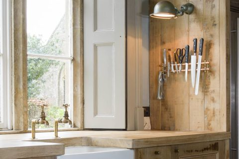 Rustic oak kitchen with large stainless steel fridge freezer and large sunken ceramic sink.