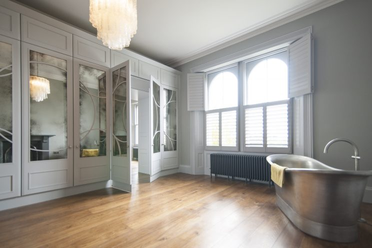 Art Deco inspired white wardrobes with stainless steel bath
