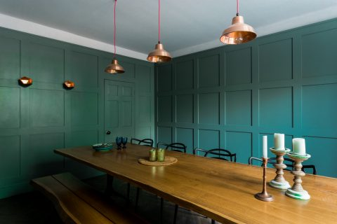 Green interior door and panelled dining room
