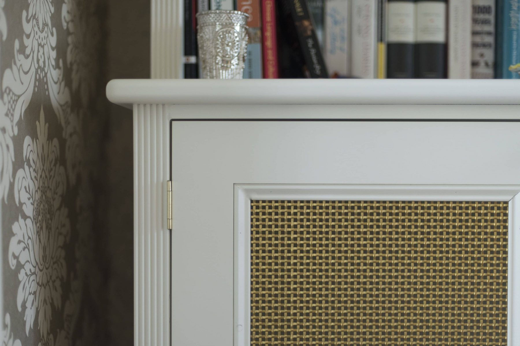 White bookcase with brass grille