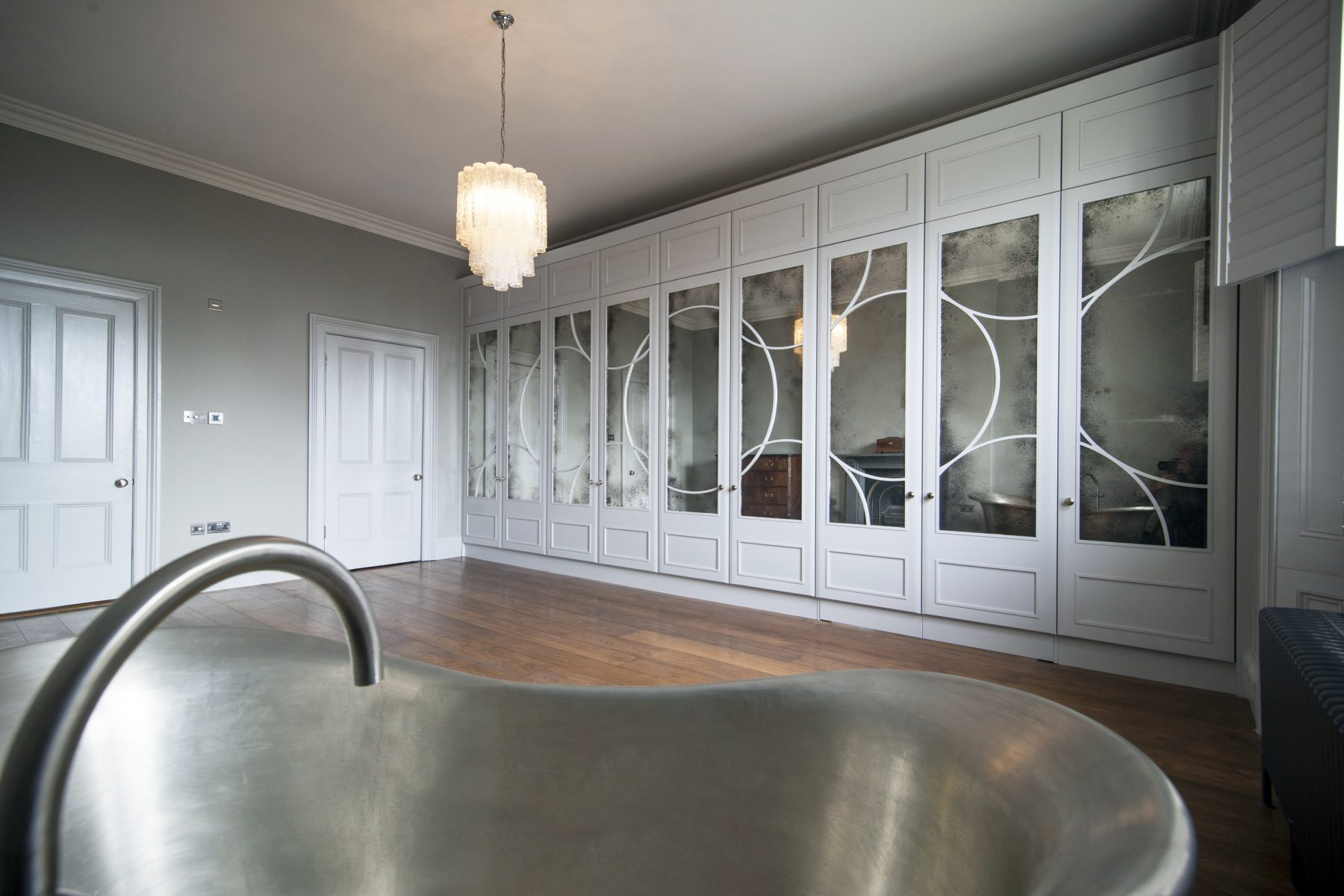 White art deco inspired wardrobes with stainless steel bath