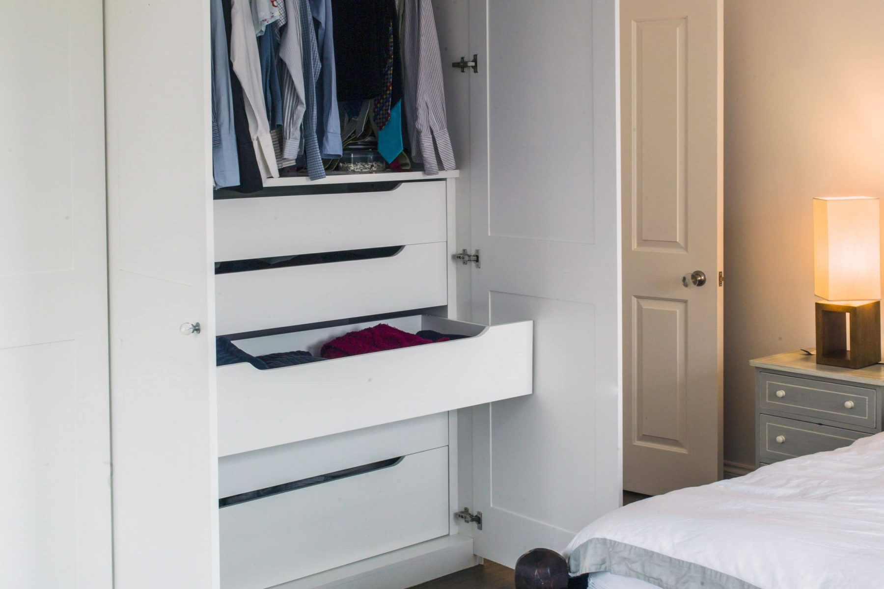 White fitted wardrobe with drawers in master bedroom
