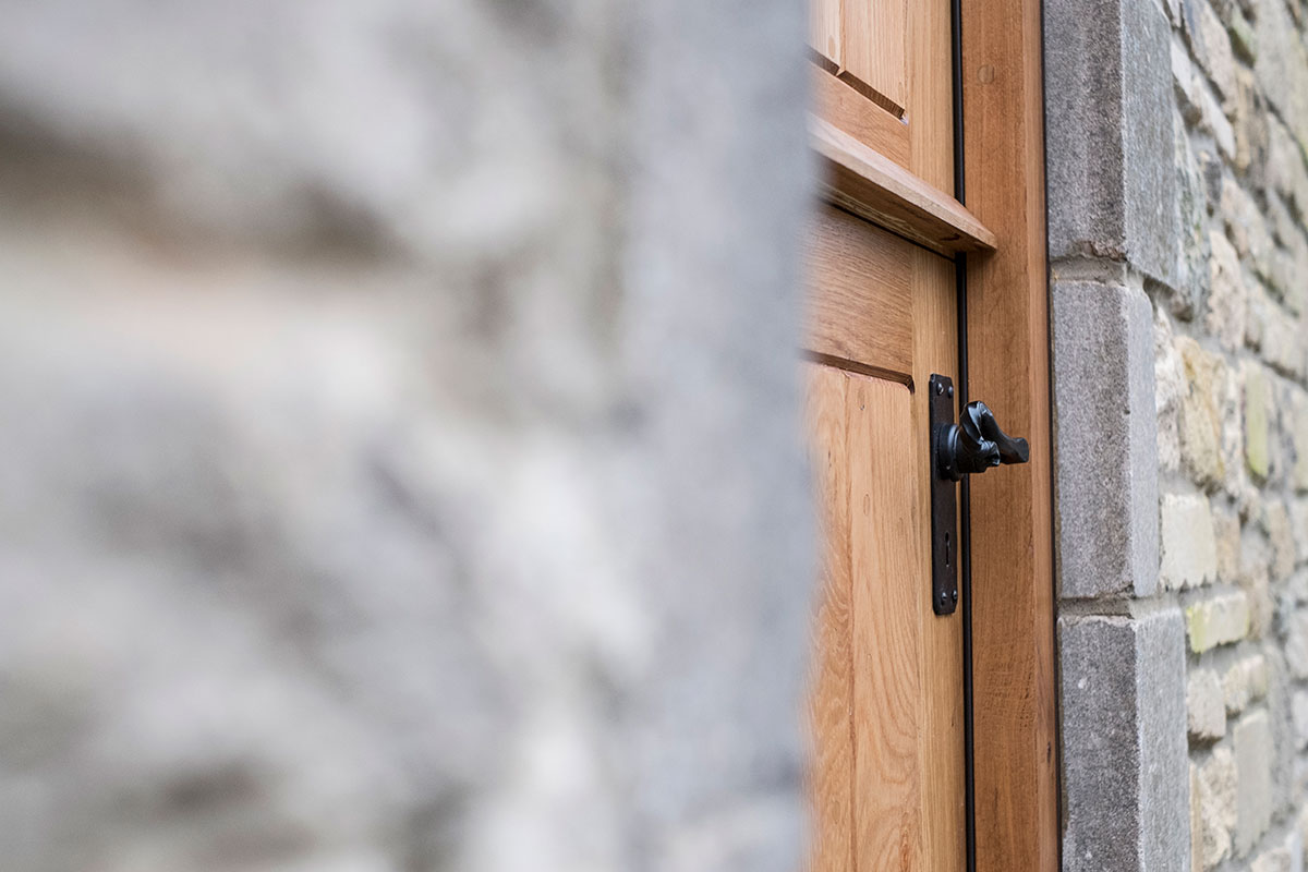 Oak exterior door in stone wall