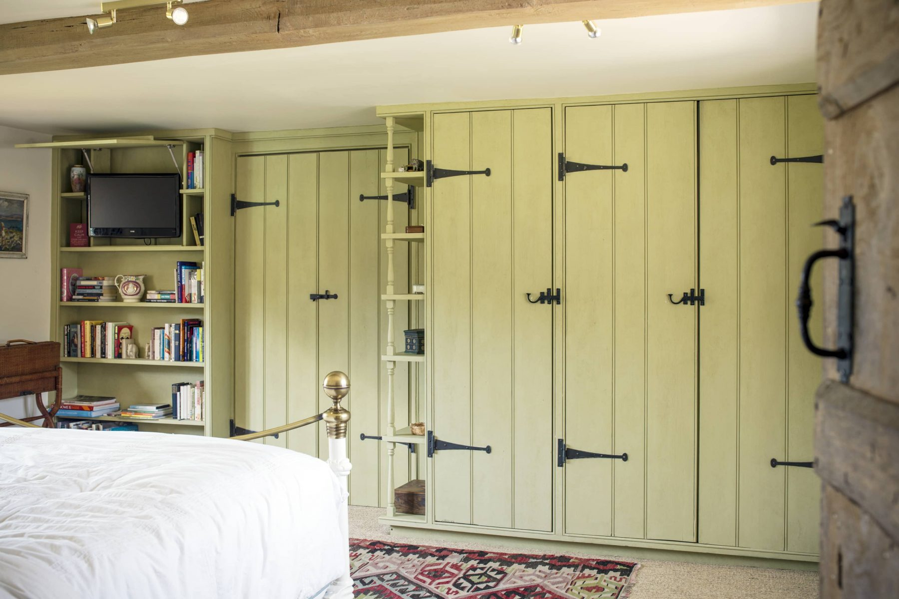Country style wardrobe in bedroom with bespoke ironmongery