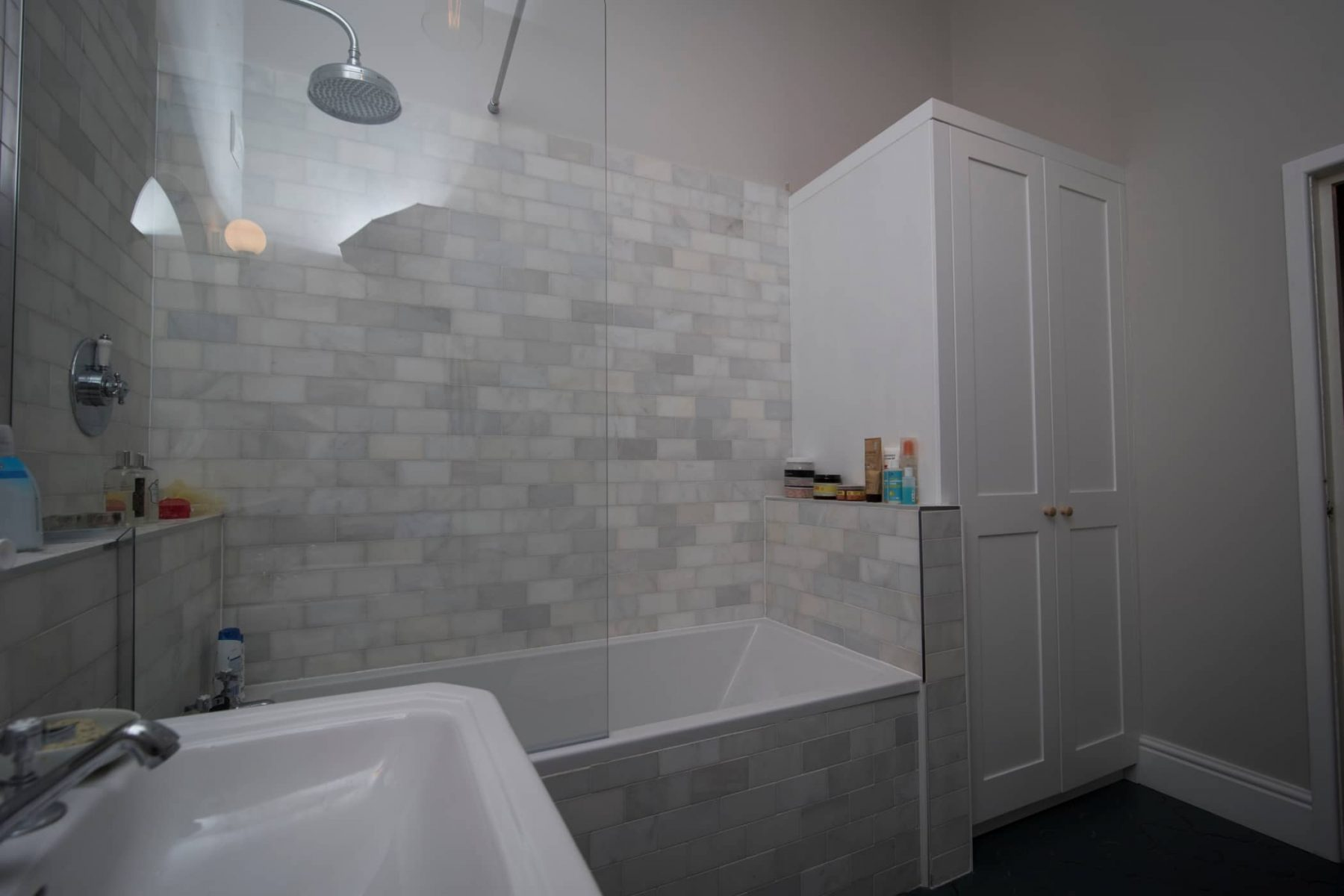 White fitted bathroom cupboards with tiled walls