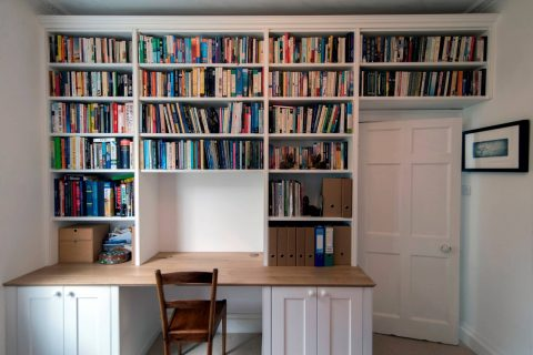 Painted study room with large wall length fitted bookcases