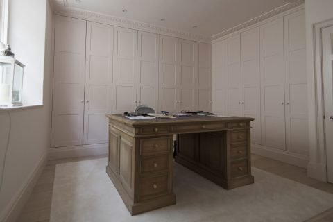 Large fitted pink wardrobes in study