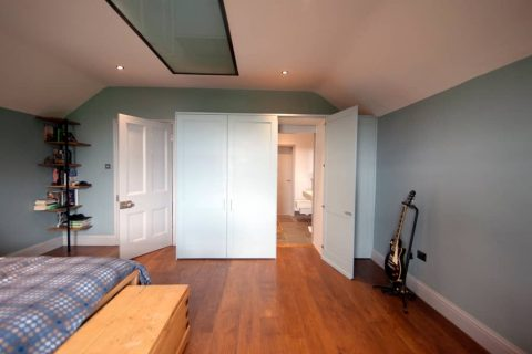 Fitted wooden wardrobe in bedroom