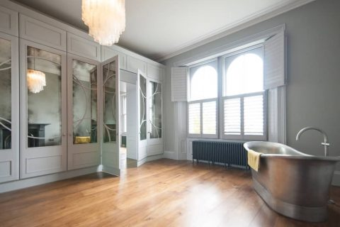 Art Deco inspired wardrobes in large bathroom with wooden flooring and white window shutters