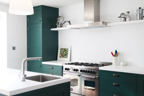 Designer white corian counter top in green shaker kitchen