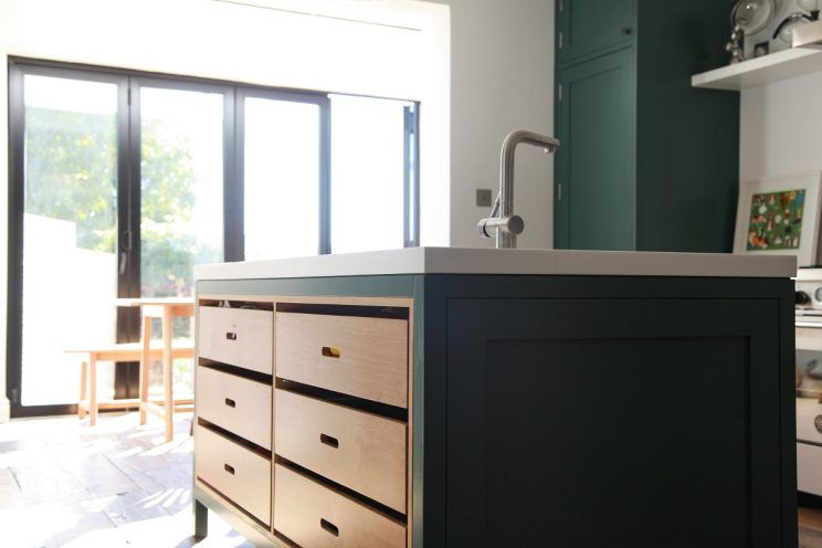 Green shaker kitchen with white Corian worktop