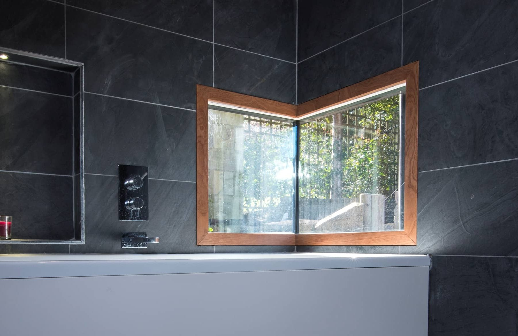 Unique corner window in dark tiled bathroom