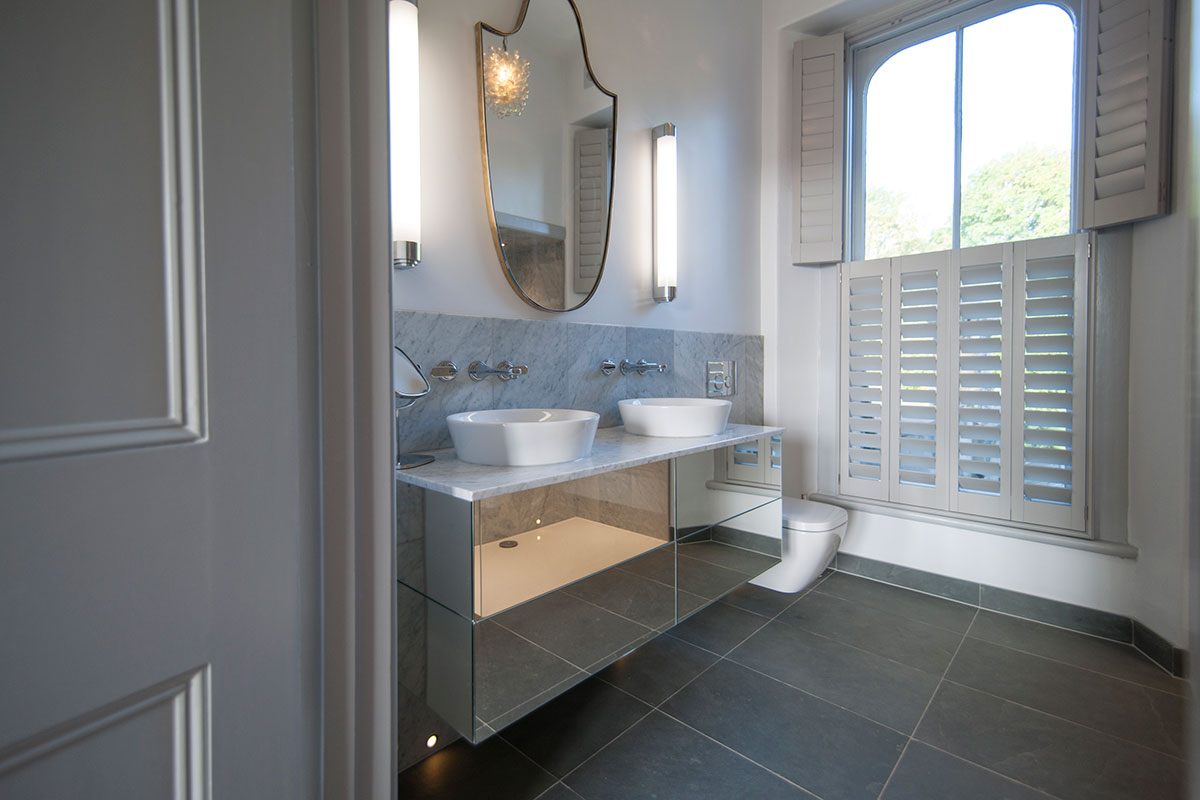 Mirror cabinets in grey and white bathroom with bespoke shutters