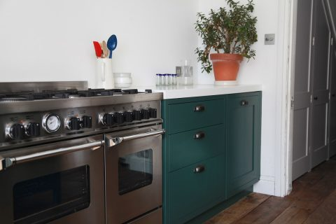 Large silver range cooker in green shaker kitchen