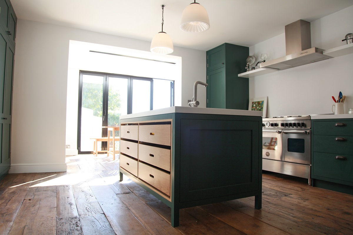 Green cabinets with silver range cooker and white walls