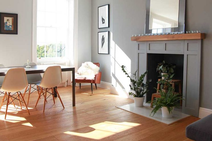 Light grey walls and fireplace with red arm chair