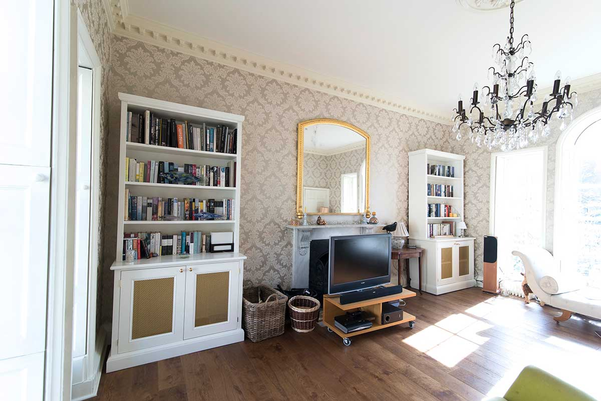 Bespoke white cabinets with glass chandelier and ornate wallpaper