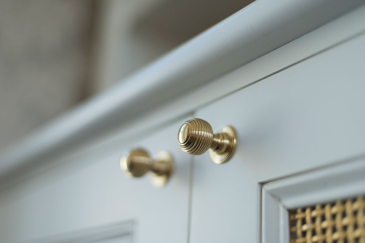 Gold ring knobs on white cabinets