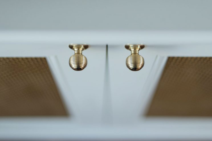 Gold ring knobs on white cabinet