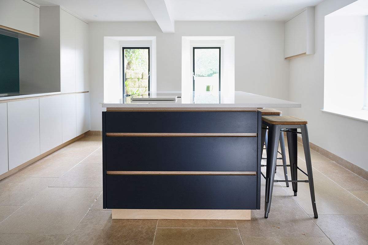 Dark blue kitchen island in white room with Silestone counter top