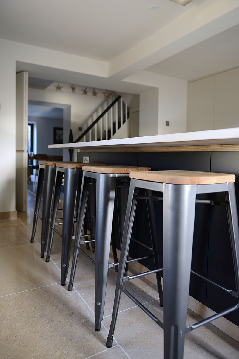 Modern kitchen island with Silestone counter top and metal stools