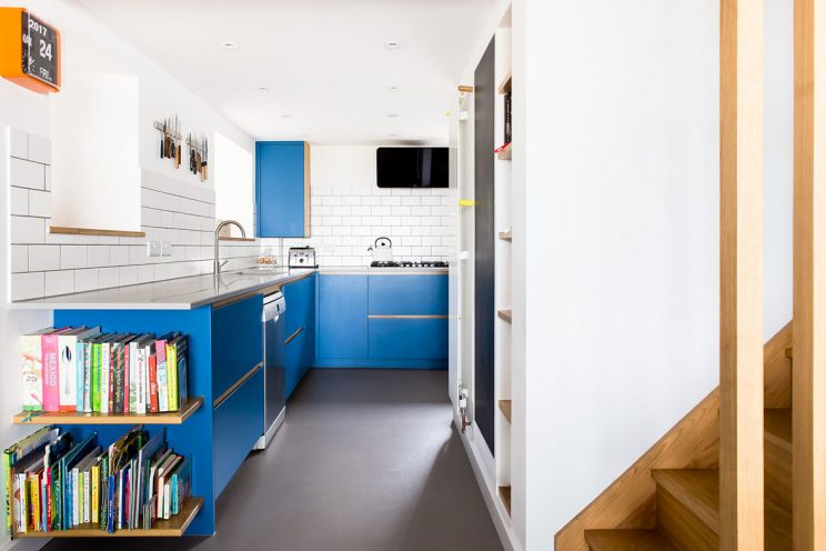 Open plan blue kitchen with walkway