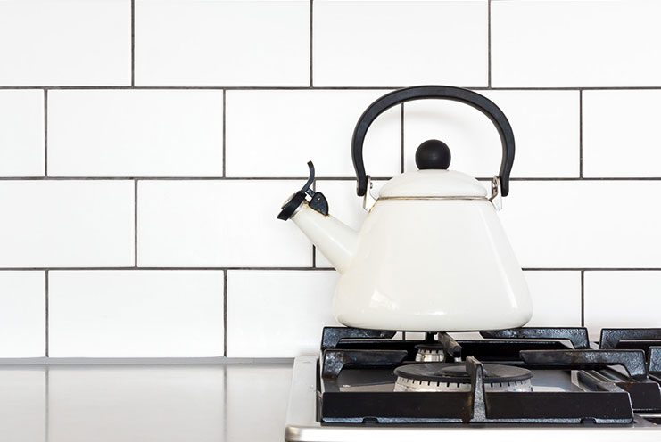 Traditional cream small kettle on gas hob