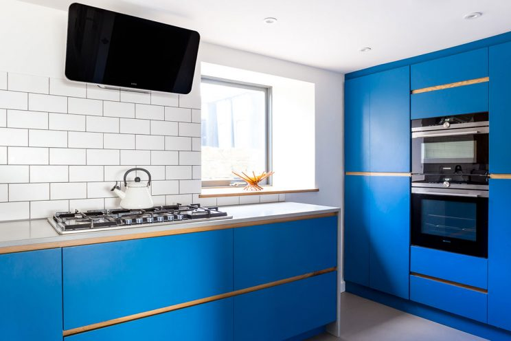 Electric blue modern kitchen with traditional hob cream kettle