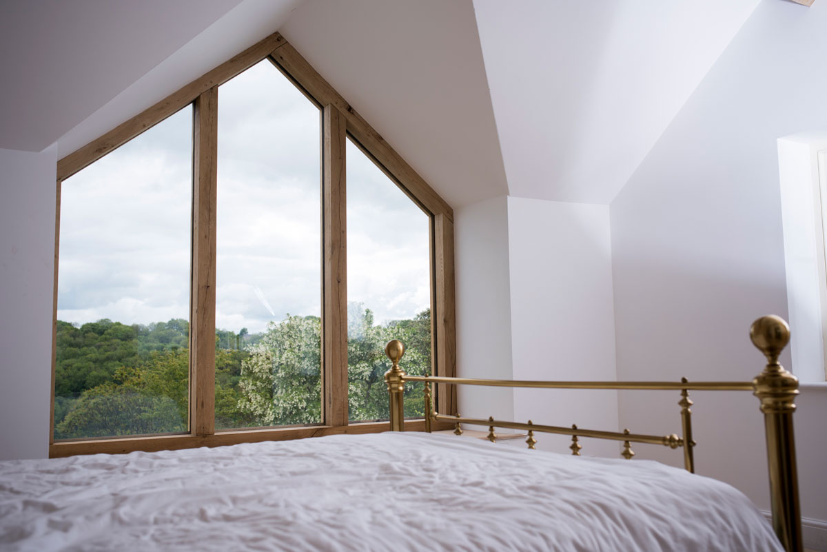 Gable end oak window in master bedroom with brass bed post