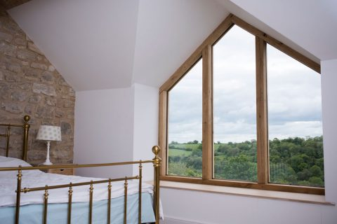 Gable end window made of oak in a master bedroom