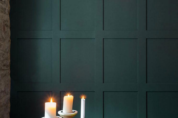 The copper lamp compliments the forest green panelling