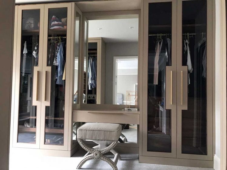 Luxurious dressing room with glazed fitted wardrobes ...