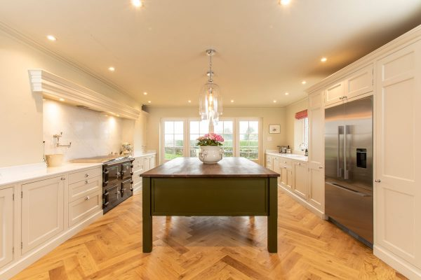 Traditional kitchen with a walnut island finished in Invisible Greene