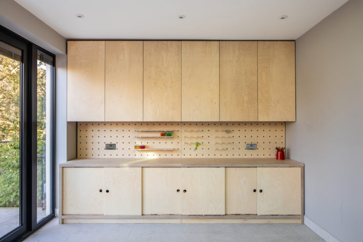 Built-in cupboards with pegboard shelves - kids craft station in birch ply